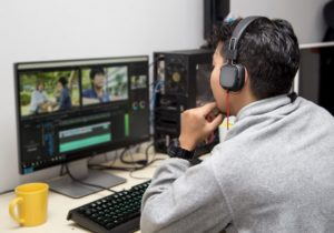 man wearing headphones and editing a video